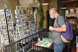British tourist buying postcards in Uzes, Gard, Southern France, 2021. MR