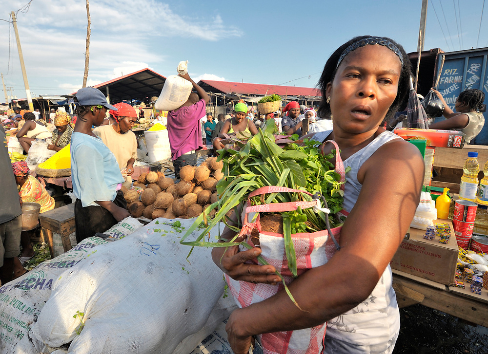 A woman buys produce in the Croix-des-Bossales market in the La Saline neighborhood of Port-au-Prince, Haiti.