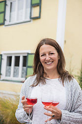 Mid adult woman holding three glasses of red wine, Bavaria, Germany