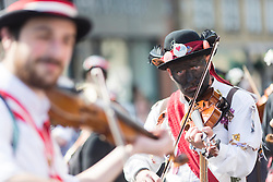 © Licensed to London News Pictures. 23/08/2015 . Uppermill , Saddleworth , Greater Manchester , UK. <br /> The Saddleworth Ruschart Festival in Uppermill today (Sunday 23rd Aug 2015).<br /> A rushcart built of moorland rushes is pulled by Morris Dancers from Uppermill village square to St Chad's Church.  The tradition arises from the laying of rushes on the church floor to keep it warm in winter.<br /> Silurian group play music.<br /> <br /> Photo credit : Photographers Chris Bull / LNP