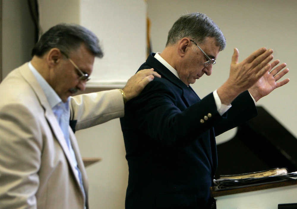Pastor Vincent Guerra (L) prays at the Sunday church service at Tried-Stone Christian Center with John Cundiff (R), a Virginia Tech professor who had one of his students killed in the tragedy in Blacksburg, Virginia April 22, 2007.  REUTERS/Rick Wilking (UNITED STATES)