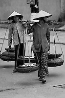 Two old women carrying baskets over their shoulders walking along the streets of Hoi An, Vietnam.