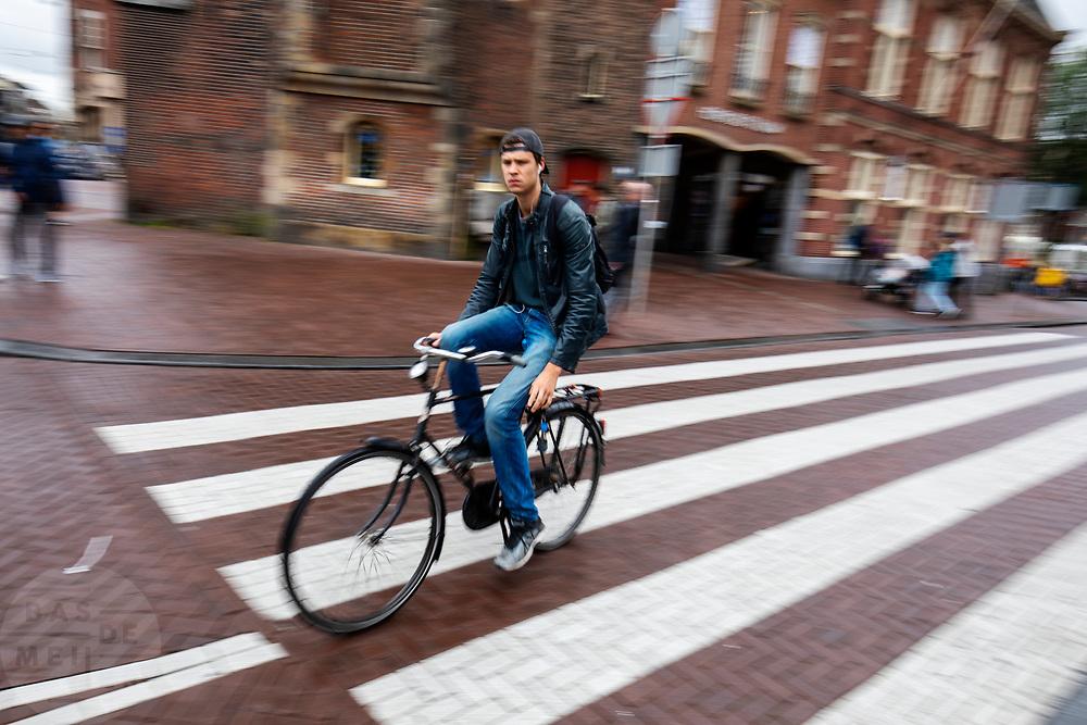 Een jongen rijdt op de fiets over het Muntplein in Amsterdam.<br /> <br /> A boy cycles at the Munt Square in Amsterdam.