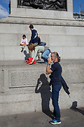 A woman tourist attempts to climb on to the plinth of Nelson's Column in Trafalgar Square, on 10th August 2017, in London, England.