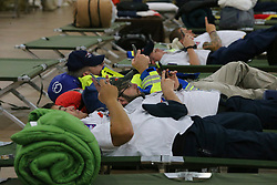 August 26, 2017 - San Antonio, Texas, USA - First responders get some rest and check phones in a building near the Freeman Expo Hall as Hurricane Harvey passes through San Antonio. The area is a staging hub for emergency personnel from all over the United States and is a temporary home for emergency wokers from Texas, Missouri, Ohio, Utah and other states. The storm is moving to the north. (Credit Image: © San Antonio Express-News via ZUMA Wire)