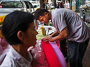 "18 JANUARY 2017 - BANGKOK, THAILAND: A man cuts red paper that a traditional Chinese calligrapher uses to draw New Years greetings in Bangkok's Chinatown district, before the celebration of the Lunar New Year. Chinese New Year, also called Lunar New Year or Tet (in Vietnamese communities) starts Saturday, 28 January. The coming year will be the ""Year of the Rooster."" Thailand has the largest overseas Chinese population in the world; about 14 percent of Thais are of Chinese ancestry and some Chinese holidays, especially Chinese New Year, are widely celebrated in Thailand.      PHOTO BY JACK KURTZ"