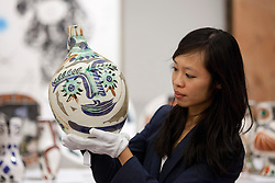 © Licensed to London News Pictures. 13/09/2013. London, UK. A Sotheby's employee holds 'Visage aux yeux rieurs' (1969) (est. GB£8,000-12,000) a earthenware clay pitcher by Pablo Picasso at the press view for Sotheby's 'Prints and Multiples Sale' on New Bond Street in London today (13/09/2013). The auction, set to take place on the 17th of September, includes works by Munch, Rembrandt, Basquiat, Warhol and Picasso. Photo credit: Matt Cetti-Roberts/LNP