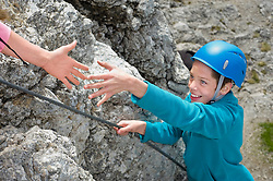 Hand helping teenage boy climbing Alps reaching