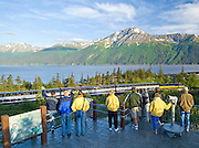 People at Bird Point overlook watch the  Alaska Railroad train passing by Turnagain Arm and the Chugach mountains, Alaska