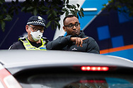A relative of locked in resident at 120 Racecourse Road speaks to police amid a full and total lockdown of 9 housing commission high rise towers in North Melbourne and Flemington during COVID-19 on 5 July, 2020 in Melbourne, Australia. After 108 new cases where uncovered overnight, the Premier Daniel Andrews announced on July 4 that effective at midnight last night, two more suburbs have been added to the suburb by suburb lockdown being Flemington and North Melbourne. Further to that, nine high rise public housing buildings in these suburbs have been placed under hard lockdown for a minimum of five days, effective immediately.  Residents in these towers will not be allowed to leave their units for any reason. Police will be stationed at every entry and exit point, every level, and they will also surround these locations preventing any movement in, or out. There is a total of 1354 units and over 3000 residents living in these buildings including the states most vulnerable people. These new restrictions will remain in place for fourteen days with fears of further lockdowns to come. The Government have stressed that if Victorians do not follow the basic COVIDSafe rules, the whole state will go back in to lockdown. (Image by Dave Hewison/ Speed Media)