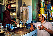 Chatting over chai, tea seller and customer exchange market gossip, Peshawar, Pakistan