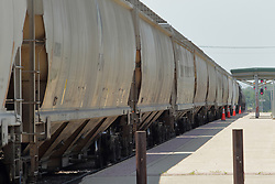 A freight train pulling hoppers travels past the Amtrak Depot in Galesburg Illinois