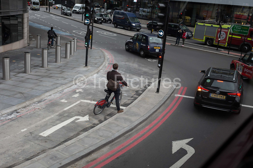 A cyclist waits for a green light to turn right at the junction of Westminster Bridge Road and Lambeth Palace Road, on 15th January 2019, in London, England.
