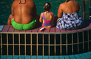 Two obese parents and their normal weight child sit with their backs to the viewer on the edge of a pool on the open deck of the Fun Ship Ecstasy belonging to Carnival Cruises, as it sails through the Gulf of Mexico. The two adults and the girl wear bathing costumes and their tanned skin is exposed to the sun. They are sitting on the rectangular pool-side tiles taking in the atmosphere and the blue water that they're facing. We see the comparison of healthy youth and oversized adulthood, the parents' wide posteriors dwarf the normal size of their child.