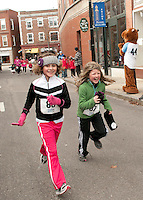Sydney Phelps and Megan Goodridge approach the finish line of the Frozen 5k Saturday morning to benefit the WLNH Children's Auction.   (Karen Bobotas/for the Laconia Daily Sun)