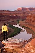A visitor views the Colorado River from Potash Road, Island in the Sky District, Canyonlands National Park, near Moab, Utah.  (model released)