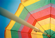 Close up of rainbow colored beach umbrella and pole in front of blue sky