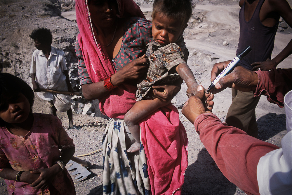 A boy's fingernail is painted with a permanent marker to indicate he has received his polio vaccination, during a round to vaccinate the children of the workers in the stone mines, some thirty km' outside the city of Jodhpur in Rajasthan.