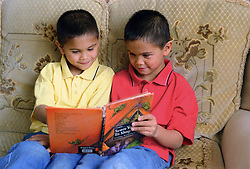 Twin boys sitting on sofa reading story book together,