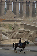 A young Egyptian man rides a horse in front of the ancient Egyptian columns of Luxor Temple, Luxor, Nile Valley, Egypt. Rides are offered in the nearby town square to young tourists who can walk around the public space. The temple behind was built by Amenhotep III, completed by Tutankhamun then added to by Rameses II. Towards the rear is a granite shrine dedicated to Alexander the Great and in another part, was a Roman encampment. The temple has been in almost continuous use as a place of worship right up to the present day.