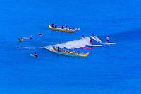 Surfers and outrigger canoes in the waters off Waikiki Beach, Honolulu, Oahu, Hawaii, USA
