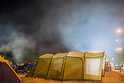 The hot and dry conditions make the site very dusty and a huge cloud floats over the forest and campsite from one of the dance areas in the woods - The 2018 Latitude Festival, Henham Park. Suffolk 15 July 2018