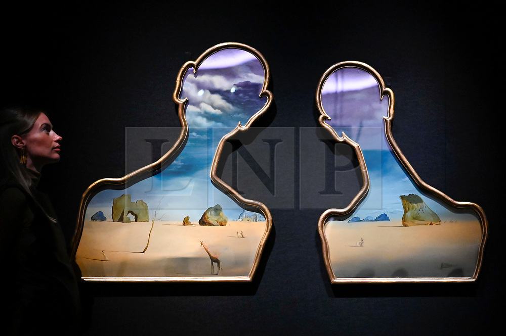 """© Licensed to London News Pictures. 29/01/2020. LONDON, UK.  A staff member poses next to """"Couple aux têtes pleines de nuages"""", 1937, by Salvador Dalí (Est. £7-10m).  Preview of Bonhams Impressionist and Modern Art Sale at New Bond Street which will take place on 26 March 2020.  Photo credit: Stephen Chung/LNP"""