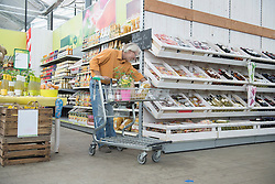 Customer shopping in supermarket with shopping trolley, Augsburg, Bavaria, Germany