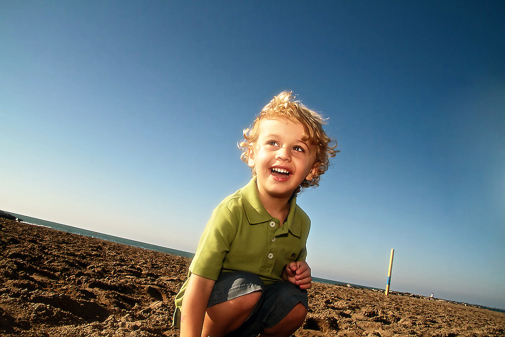 Boy plays at beach on a sunny day.