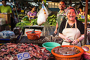 """26 SEPTEMBER 2012 - BANGKOK, THAILAND:  A meat vendor in Khlong Toey Market in Bangkok. Khlong Toey (also called Khlong Toei) Market is one of the largest """"wet markets"""" in Thailand. The market is located in the midst of one of Bangkok's largest slum areas and close to the city's original deep water port. Thousands of people live in the neighboring slum area. Thousands more shop in the sprawling market for fresh fruits and vegetables as well meat, fish and poultry.    PHOTO BY JACK KURTZ"""
