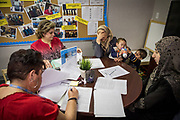 (From L) Marta Tudela, a CARIBE Refugee Program intake counselor, and resettlement case manager Rana Al Sarraf assist Nahed Kanj, 22, and sister-in-law Kawthar Alsaloum, 23, with applications for subsidized childcare at the CARIBE office in Tampa, Florida, U.S. Al Sarraf was instrumental in helping the Alsaloum family with tedious paperwork in the early months.