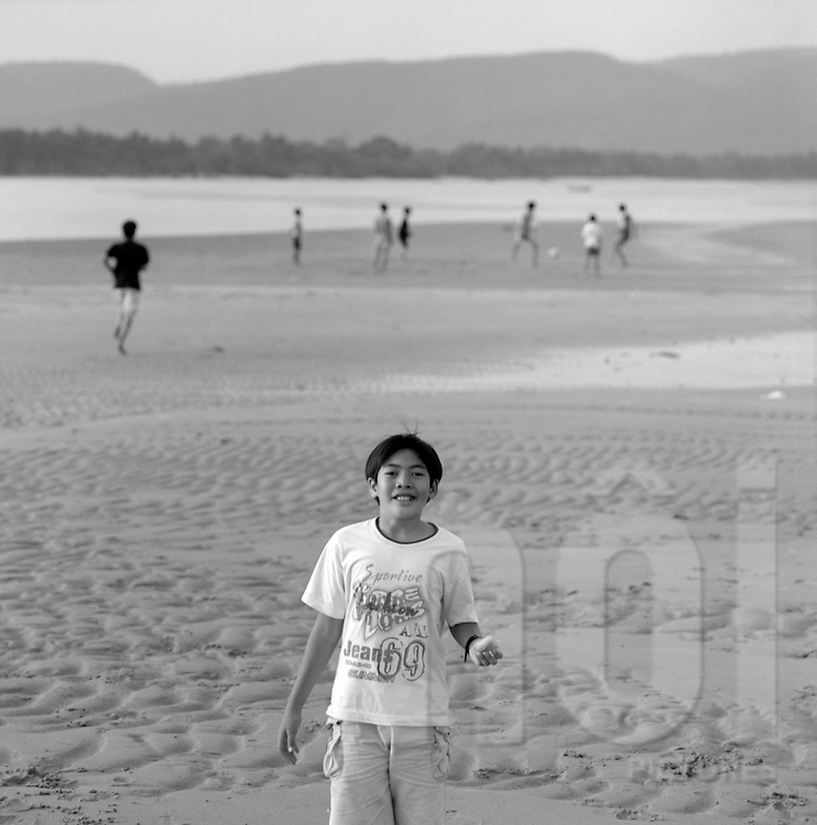 A young boy plays football on the sand during low tide in Dinh Ba, Phu Quoc island, Vietnam. 2005