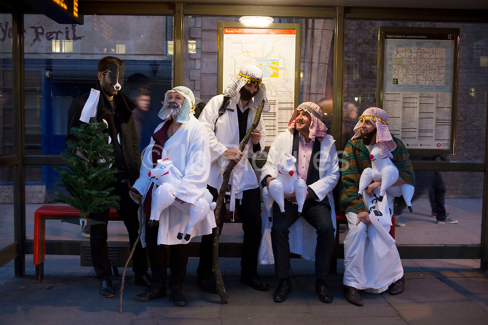 Work colleagues in fancy dress for their Christmas party, dressed up as three / four wise men, wait at a bus stop. They are in happy mood having fun looking ridiculous. London, UK.