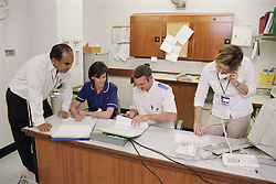 Doctor talking to deputy sister; staff nurse and dietician at workstation on spinal unit of hospital,