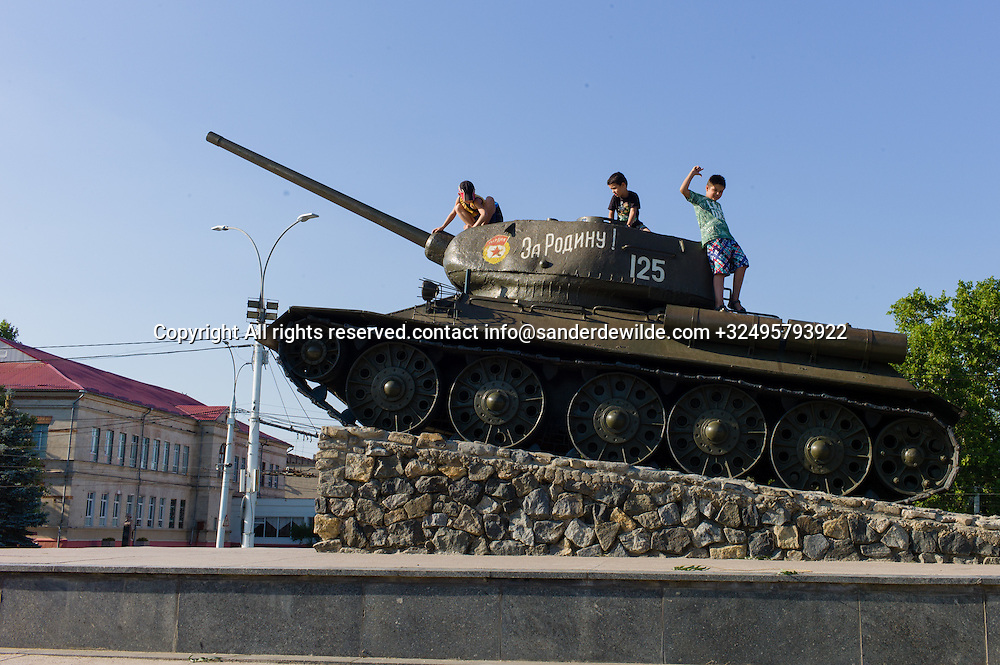 """20150825  Moldova, Transnistria, Tiraspol.At the bank of the Dniestr River –<br /> along the """"25th October Street"""" – opposite<br /> the parliament building with the statue of<br /> Lenin is the """"Monument Square"""" with a<br /> Soviet T-34 tank,.boys climbed the tank and play."""