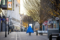 © Licensed to London News Pictures. 25/12/2020. Manchester, UK. A man who is living rough , walks up Market Street wrapped in a sleeping bag , in Manchester City Centre on Christmas Day . Photo credit: Joel Goodman/LNP