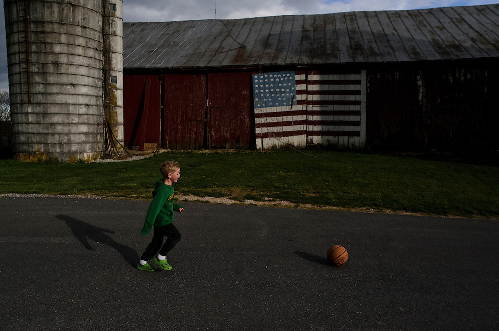 photo by Matt Roth.Wednesday, April 11, 2012..Miles Shriver chases a basketball past his grandparents' barn door. Ron Shriver's family painted the U.S. flag in honor of Ron a few weeks before he left for bootcamp -- in the summer of 2001...Ron Shriver grew up on a large farm house in Pleasant Valley, Maryland, a small township outside Westminster. After his lease was up, he moved back to his parent's home with his two children Rory and Miles, living temporarily in their basement before graduating from McDaniel College in May. After tossing his graduation cap, he and his children will drive cross country to meet up with his wife who has been working on her graduate degree in Alaska. ..Ron Shriver is a retired marine staff sergeant. He is also the first in his family to attend college, thanks to the New G.I. Bill. His wife, a fellow retired Marine, is finishing up graduate school in Alaska. After Ron gets his undergraduate degree from McDaniel College in May, he plans to drive to Alaska with is two children Rory, 6, and Miles, 5. For the move Ron got rid of most of his family's belongings, and after his lease was up, he and his children moved back into his parent's farmhouse.