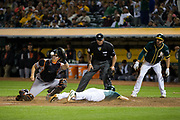 Oakland Athletics shortstop Chad Pinder (18) beats a tag at home by San Francisco Giants catcher Nick Hundley (5) to score a run at Oakland Coliseum in Oakland, California, on July 31, 2017. (Stan Olszewski/Special to S.F. Examiner)
