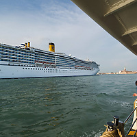 VENICE, ITALY - MAY 02:  Passengers on a Vaporetto look at a Cruise ship as she sails St Mark Basin on May 2, 2011 in Venice, Italy. Giant cruise ships passing through  St Mark Basin and Giudecca Canal are causing continue controversy for the possible damages to the lagoon and Venice buildings