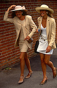 Two young women walk in a breeze towards the entrance gates to Ascot racecourse on Ladies Day at Royal Ascot racing week. Both dressed in beige browns and with wide-brimmed hats that are about to blow off, they walk with wide smiles. Royal Ascot is held every June and is one of the main dates on the sporting calendar and English social season. Over 300,000 people make the annual visit to Berkshire during Royal Ascot week, making this Europe's best-attended race meeting. There are sixteen group races on offer, with at least one Group One event on each of the five days. The Gold Cup is on Ladies' Day on the Thursday. There is over £3 million of prize money on offer.