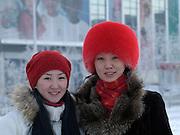 Jakutische Frauen mit Kopfbedeckung geschützt gegen die extreme Kaelte in der Innenstadt von Jakutsk. Jakutsk wurde 1632 gegruendet und feierte 2007 sein 375 jaehriges Bestehen. Jakutsk ist im Winter eine der kaeltesten Grossstaedte weltweit mit durchschnittlichen Winter Temperaturen von -40.9 Grad Celsius. Die Stadt ist nicht weit entfernt von Oimjakon, dem Kaeltepol der bewohnten Gebiete der Erde.<br /> <br /> Two yakut women protected with headgears against the extrem climate  in the city center of Yakutsk. Yakutsk was founded in 1632 and celebrated 2007 the 375th anniversary - billboard announcing the celebration. Yakutsk is a city in the Russian Far East, located about 4 degrees (450 km) below the Arctic Circle. It is the capital of the Sakha (Yakutia) Republic (formerly the Yakut Autonomous Soviet Socialist Republic), Russia and a major port on the Lena River. Yakutsk is one of the coldest cities on earth, with winter temperatures averaging -40.9 degrees Celsius.