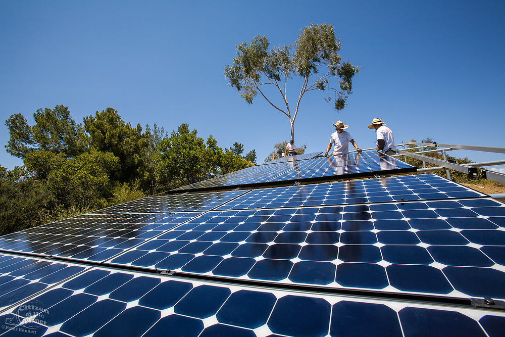 Green workers install a residential grid-tied solar array on a hillside in Malibu, California, USA