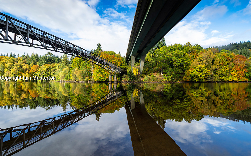Pitlochry, Scotland, UK. 12 October 2020. Autumn colours on trees surrounding Loch Faskally and footbridge and A9 road bridge reflected in water. in Pitlochry.  Iain Masterton/Alamy Live News