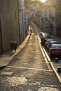 Pedestrians walk along a cobblestone street at sunset in Santiago de Compostela, Galicia, Spain.