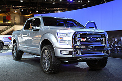 "08  February 2013: 2013 Ford Atlas Concept pickup truck. Chicago Auto Show, Chicago Automobile Trade Association (CATA), McCormick Place, Chicago Illinois<br /> <br /> FORD ATLAS CONCEPT: Calling all truck fans! If you want a glimpse at the future of Ford pickups, make sure to attend the 2013 Chicago Auto Show, Feb. 9th to Feb. 18th. On display in full glory is the Ford Atlas concept that's a rolling showcase of features that will allow pickup truck owners to work and play smarter, not harder. First off, the prototype is 238 inches in length, with a 150 in wheelbase, which are close to the dimensions of the 2013 Ford F-Series SuperCab. The handsome Atlas concept's body is constructive of high-strength steel including boron, and the exterior shape is the results of a purpose-driven design. Note the chiseled grille that uses active grille shutters to improve aerodynamics to save gas; plus the prominent wheel arches and wide stance. The 22-in alloy wheels are framed by all-terrain tires. Examples that the Atlas was inspired by Ford listening to customers at the places they work and play, are the added multiple tie-down points integrated within the cargo box walls and load floor, along with 110-volt electrical outlets in the cargo box to charge power tools. An integrated roof carrying system and hidden extendable ramps give the truck unique functionality for a variety of jobs. The tailgate step turns into cargo cradle to carry long items. Move inside the cabin and notice the ergonomic ""bullring"" steering wheel, ""floating"" instrument pods, glove-friendly buttons and controls, and thin, lightweight leather seating that allows for extra rear passenger legroom. Ford said that a next-generation EcoBoost engine with auto start-stop powers the mighty Atlas, connected with a six-speed automatic gearbox."