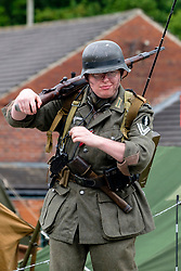 Reenactor portraying a German Soldier of World war 2 with the rank of Obergefreiter. He is carrying a Mauser K98 bolt action rifle a radio backpack and a sick grenade tucked in his belt  <br />