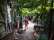13 AUGUST 2016 - BANGKOK, THAILAND:  A girl who lives in Pom Mahakan slum in Bangkok walks to a friend's home in the slum. Residents of the slum have been told they must leave the fort and that their community will be torn down. The community is known for fireworks, fighting cocks and bird cages. Mahakan Fort was built in 1783 during the reign of Siamese King Rama I. It was one of 14 fortresses designed to protect Bangkok from foreign invaders. Only of two are remaining, the others have been torn down. A community developed in the fort when people started building houses and moving into it during the reign of King Rama V (1868-1910). The land was expropriated by Bangkok city government in 1992, but the people living in the fort refused to move. In 2004 courts ruled against the residents and said the city could take the land. Eviction notices have been posted in the community but most residents have refused to move. Residents think Bangkok city officials will start evictions around August 15, but there has not been any official word from the city.      PHOTO BY JACK KURTZ