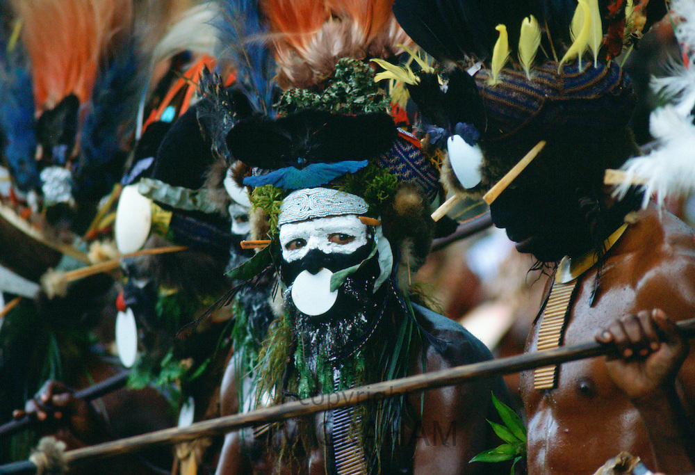 Bearded tribesmen wearing war paints and feathered headdress during  a gathering of tribes at Mount Hagen in Papua New Guinea