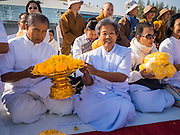 """02 JANUARY 2015 - KHLONG LUANG, PATHUM THANI, THAILAND: People pray with marigolds that would be put on the footpath for monks at Wat Phra Dhammakaya at the start of the 4th annual Dhammachai Dhutanaga (a dhutanga is a """"wandering"""" and translated as pilgrimage). More than 1,100 monks are participating in a 450 kilometer (280 miles) long pilgrimage, which is going through six provinces in central Thailand. The purpose of the pilgrimage is to pay homage to the Buddha, preserve Buddhist culture, welcome the new year, and """"develop virtuous Buddhist youth leaders."""" Wat Phra Dhammakaya is the largest Buddhist temple in Thailand and the center of the Dhammakaya movement, a Buddhist sect founded in the 1970s.   PHOTO BY JACK KURTZ"""