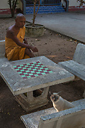 A buddhist monk relaxing from his morning chores at a temple in Aranyaprathet, Thailand